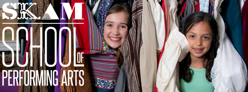Two young girls peek out from behind a rack of clothing with big smiles on their faces. The SKAM School of Performing Arts logo is in white on the right side of the image.