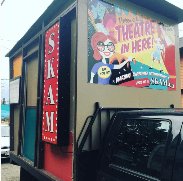"The Skam Pop-Up Theatre on the back of a pick up truck. the four walls are beige with a brightly coloured sign that says ""There's a Theatre in here!"". On the side is a long sign in red with white marquis lights and letters that say SKAM."