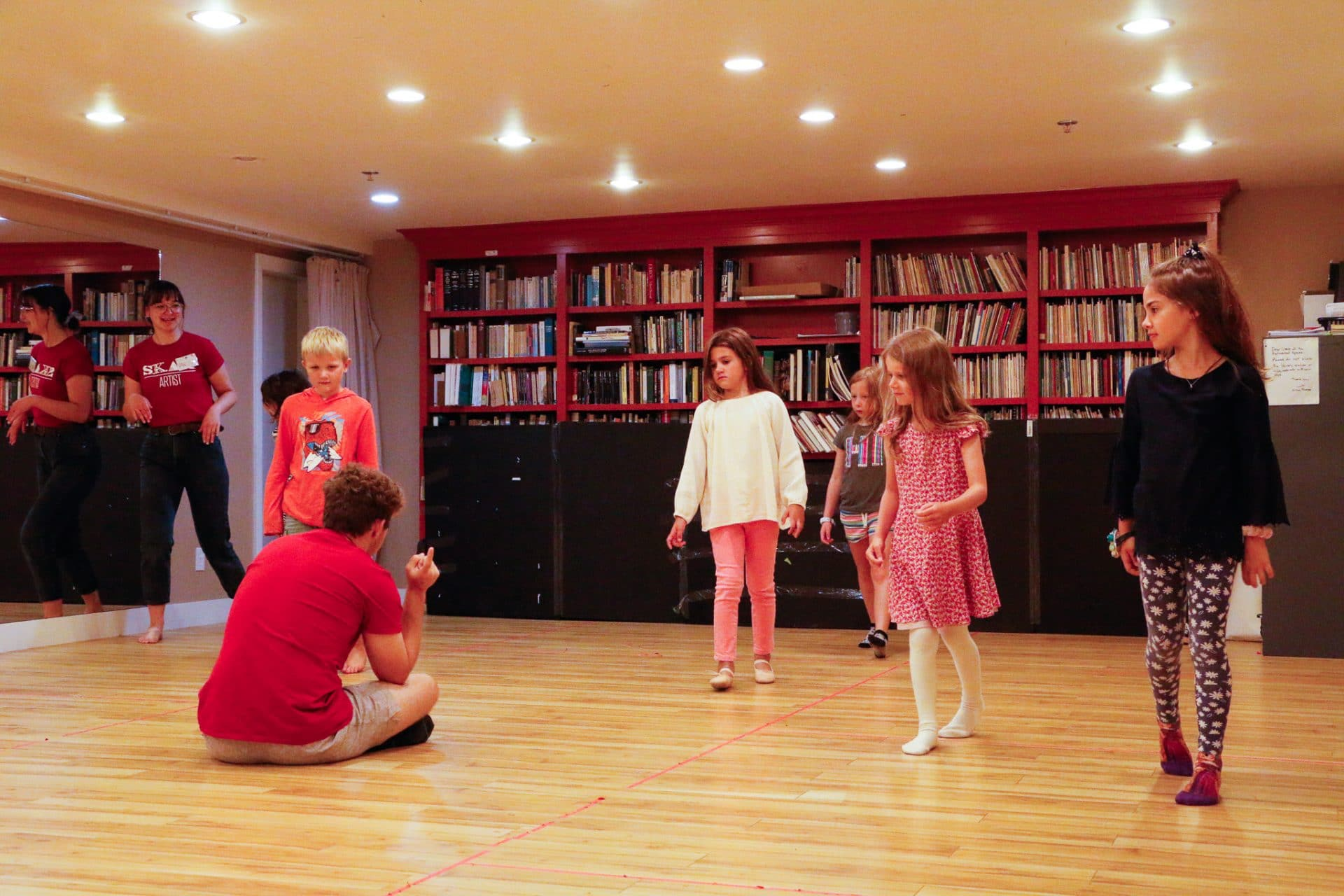 A group of kids sneak past their teacher in a studio room, as part of a game.